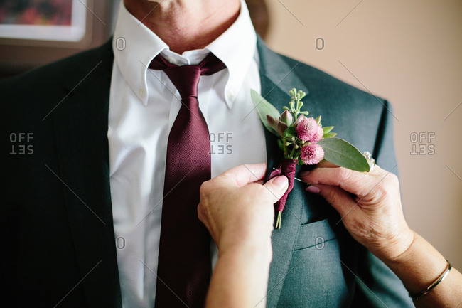 Woman attaching boutonniere to groom's jacket