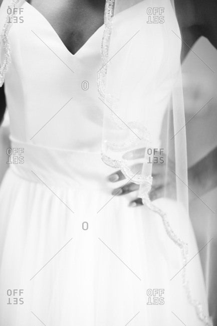 Close up of a bride standing with her hand on her hip in black and white