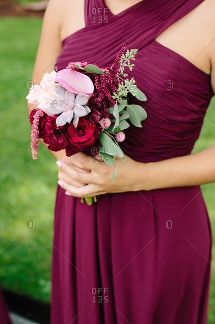 Bridesmaid wearing burgundy dress holding bouquet