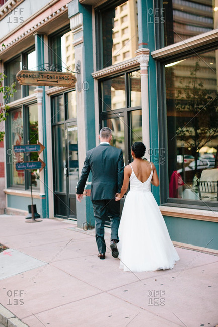 Bride and groom walking on a city street
