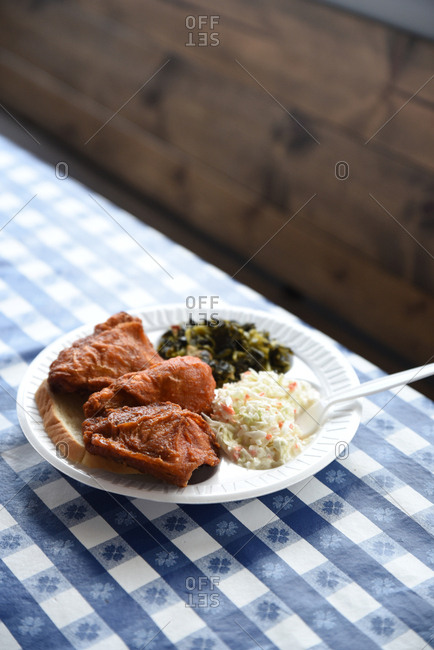 Fried chicken served with coleslaw and greens