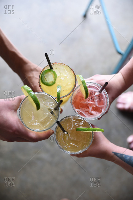 Four people toasting with cocktails