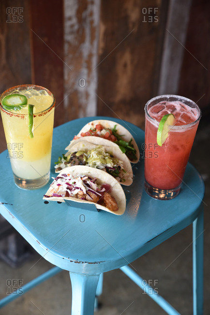 Close up of tacos on a blue stool with margaritas