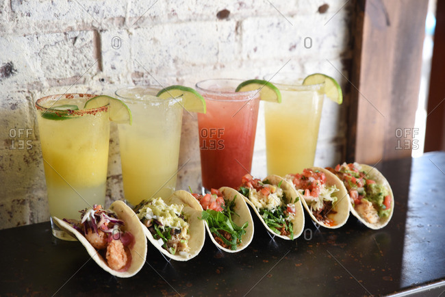 Margaritas and tacos in front of a white brick wall