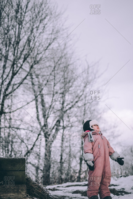 Little girl standing outside in the snow with bare trees in the background