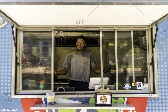 Washington D.C. - July 19, 2016: Worker smiling looking out window of a food truck