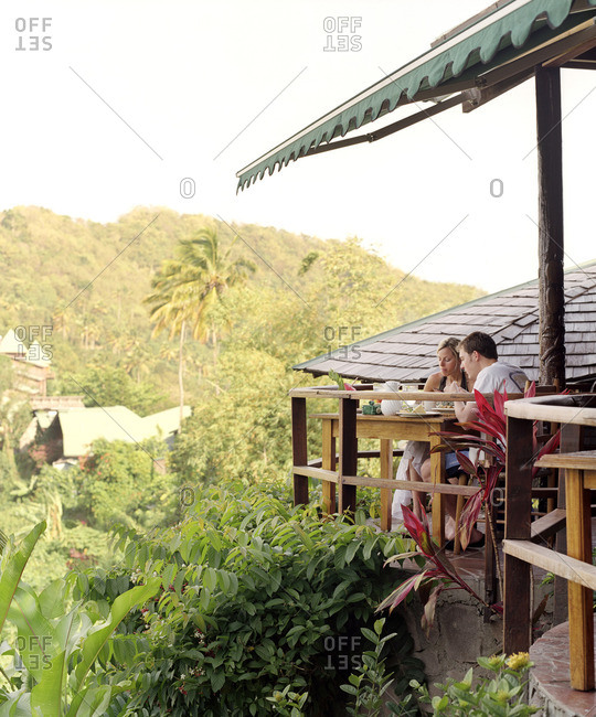 A young couple enjoys breakfast at Dasheene Restaurant  at Ladera Resort.Soufriere, St. Lucia.