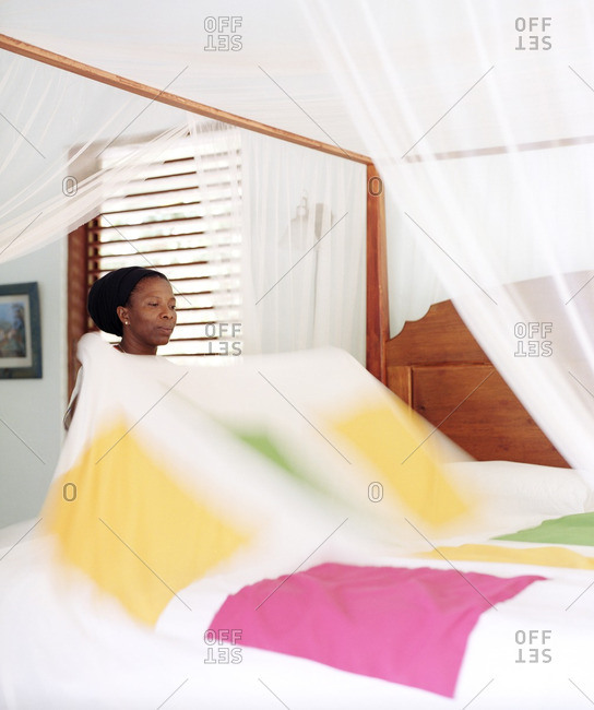 A housekeeper makes a bed in the  Hibiscus Villa at the Stonefield Estate Villa Resort in St. Lucia. Soufriere, St. Lucia.