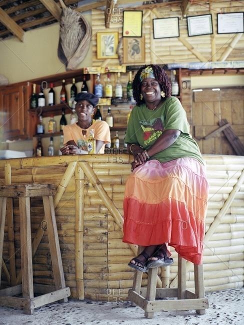The owner of Marjorie's Beach Bar on Cas En Bas beach relaxes at her bar. Cas En Bas, St. Lucia, W.I.