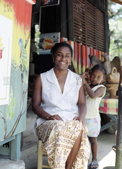 A local artist sits outside of her Living Arts Studio with her daughter. Colombette, Soufriere, St. Lucia.