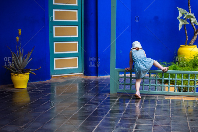Girl climbing over a railing outside a bright blue building
