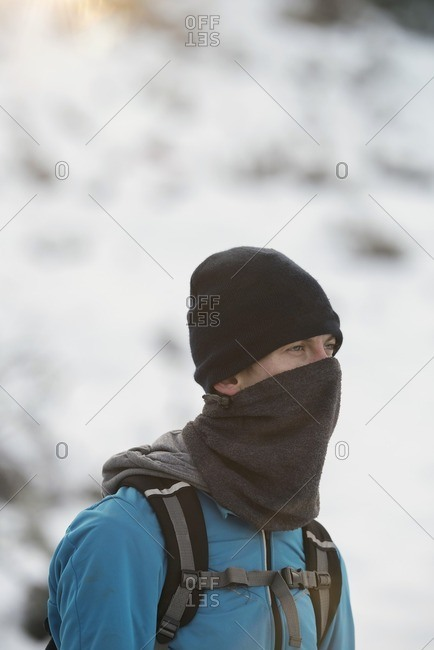 Man with woolen cap and scarf outdoor in winter.