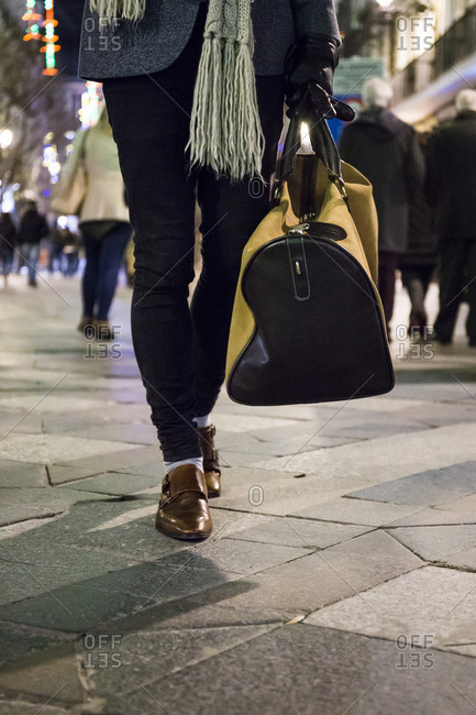 Legs of a man with a bag walking in the city at night