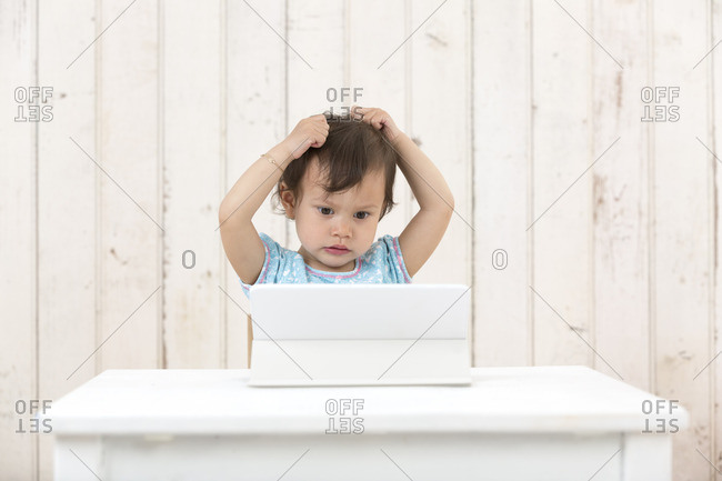 Portrait of little girl tearing her hair out while looking at laptop