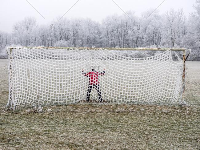 Man in soccer goal in winter