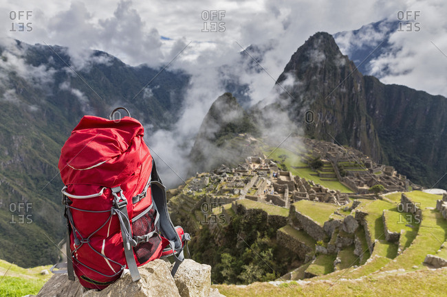 Peru- Andes- Urubamba Valley- red backpack at Machu Picchu with mountain Huayna Picchu