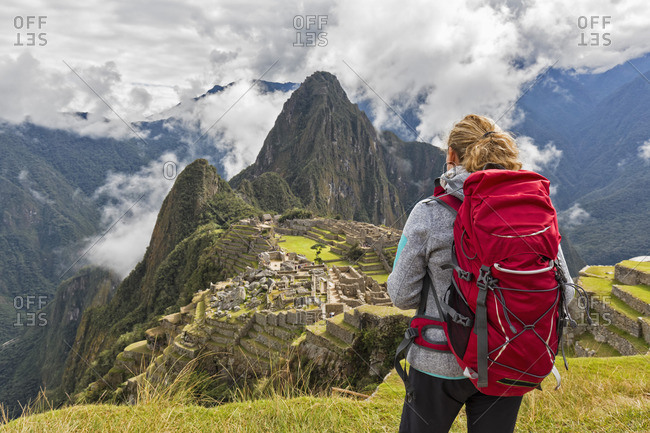 Peru- Andes- Urubamba Valley- tourist with red backpack at Machu Picchu with mountain Huayna Picchu