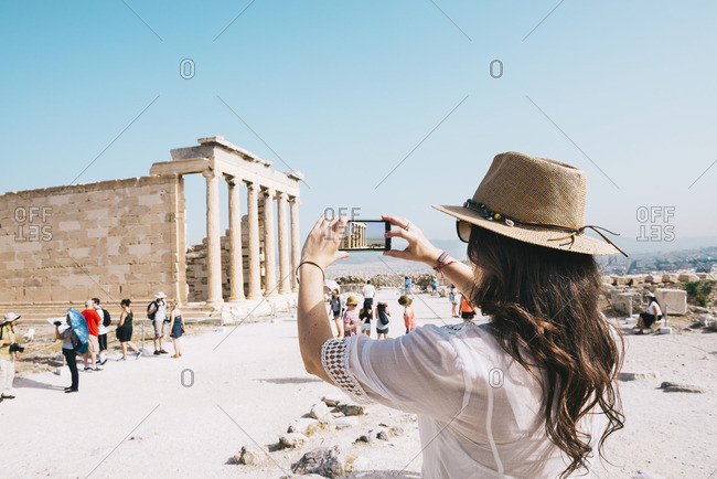 Greece- Athens- woman taking a cell phone picture of the Erechtheion temple in the Acropolis