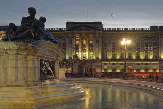 UK- London- lighted Buckingham Palace at dusk with fountain in the foreground