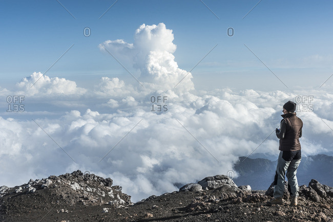 Italy- Sicily- hiker standing on Mount Etna looking at view