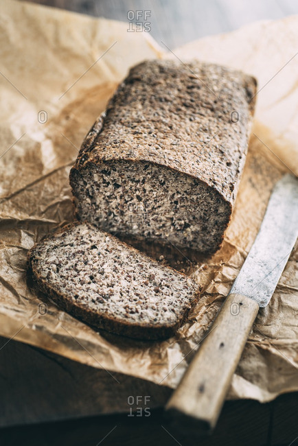 Home-baked whole meal gluten-ree bread and bread knife on brown paper