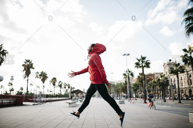 Young man in the city jumping on pavement