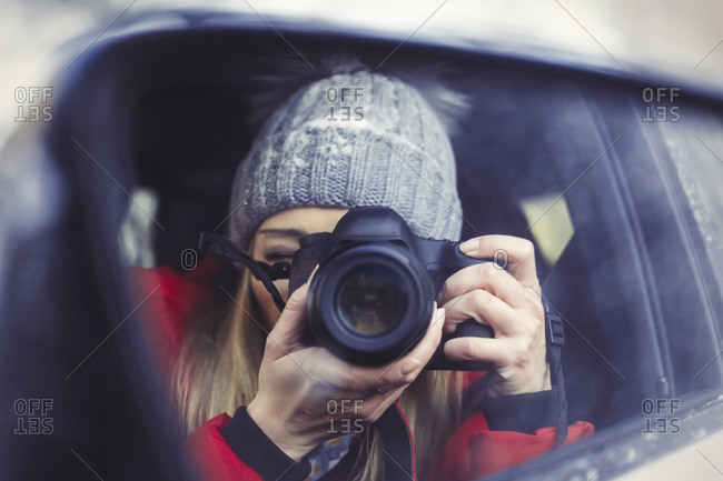 Wing mirror with mirror image of woman taking picture of herself- close-up