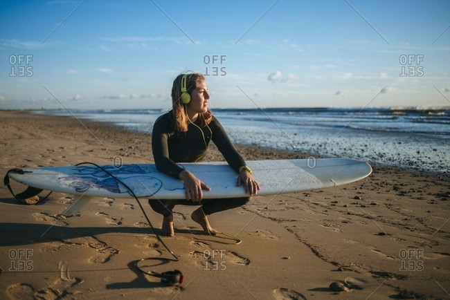 Young woman with surfboard listening music on the beach by sunset