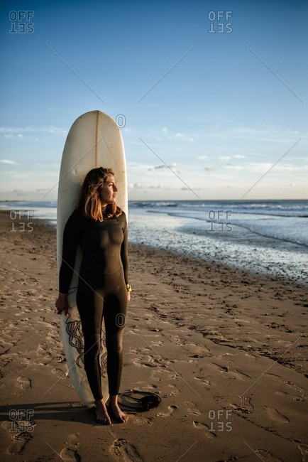 Young woman with surfboard standing on the beach watching sunset