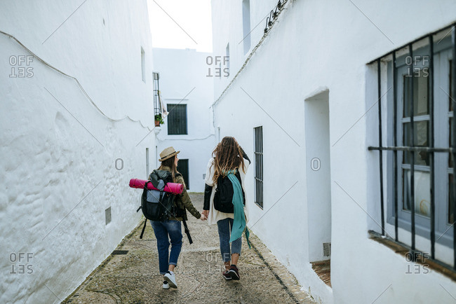 Two young women on a trip walking in a town holding hands