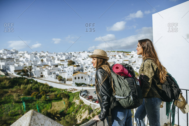 Spain- Andalusia- Vejer de la Frontera- two young women looking from balcony on the town