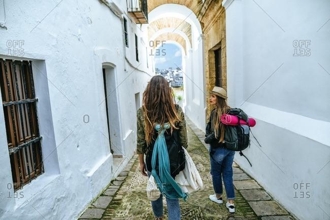 Spain- Andalusia- Vejer de la Frontera- two young women walking in the alley El Callejon de las Monjas