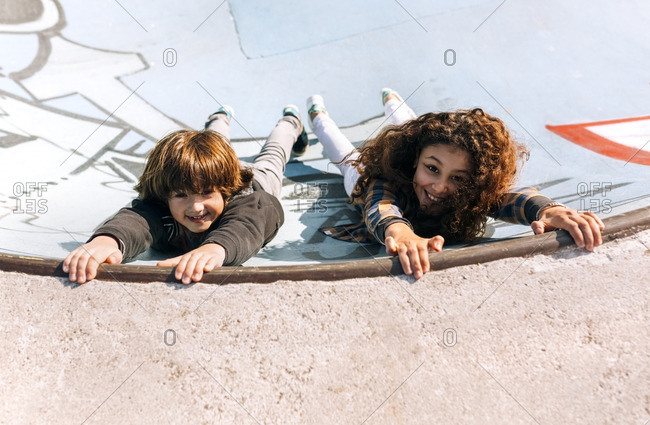 Two children playing in a skate park