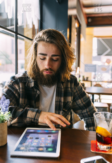 Stylish young man looking at tablet in a cafe