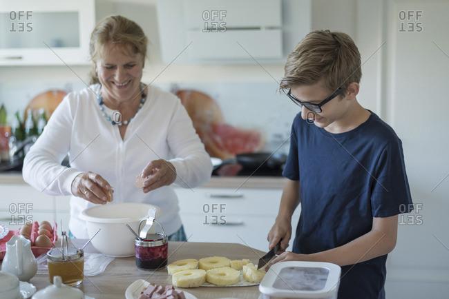 Grandson helping grandmother in kitchen