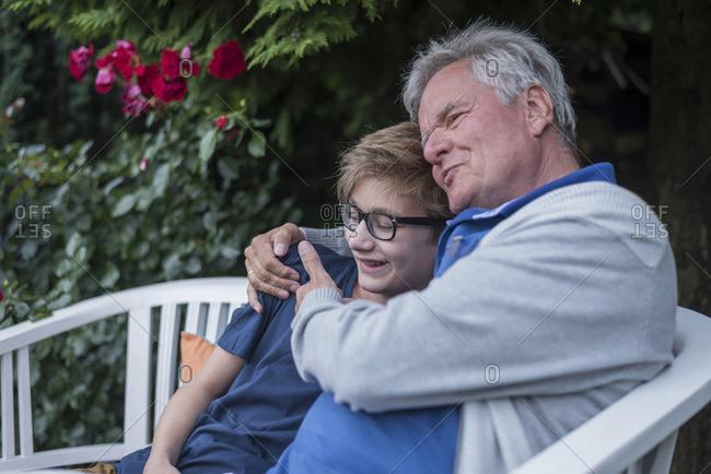 Grandfather hugging grandson on garden bench