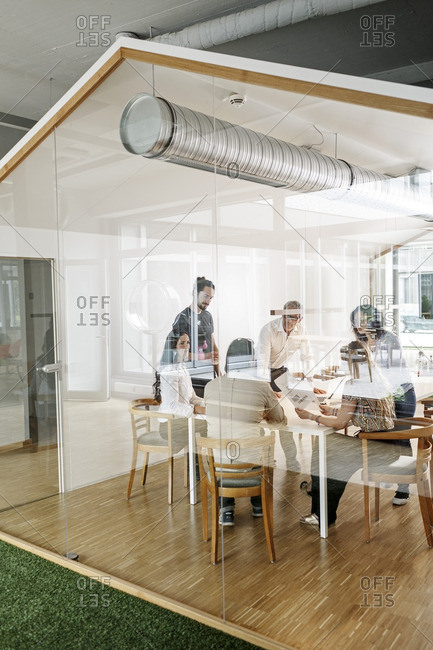 Business meeting in conference room behind glass wall