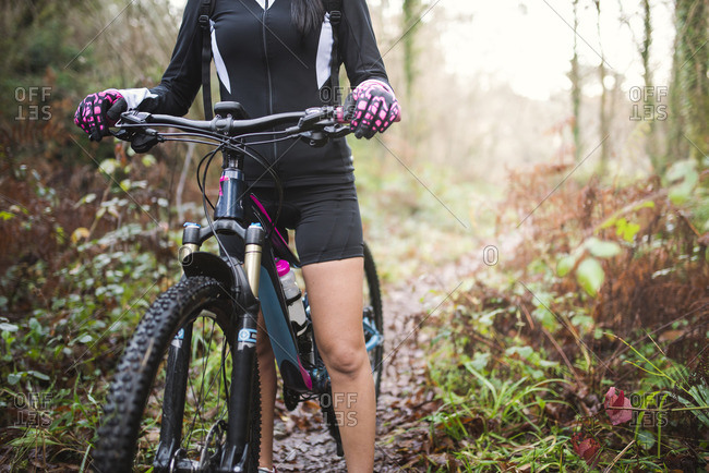 Female mountain biker on a trail in forest