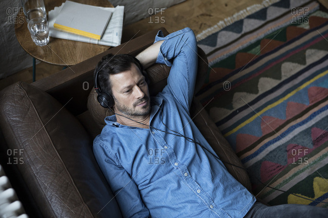 Man lying on couch- wearing head phones