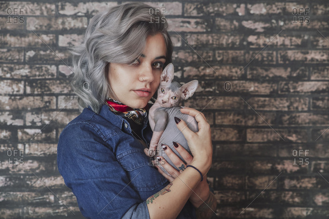 Young woman holding Sphynx cat