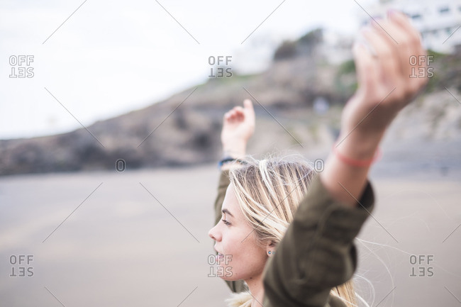 Blond young woman standing on the beach with arms outstretched looking at distance