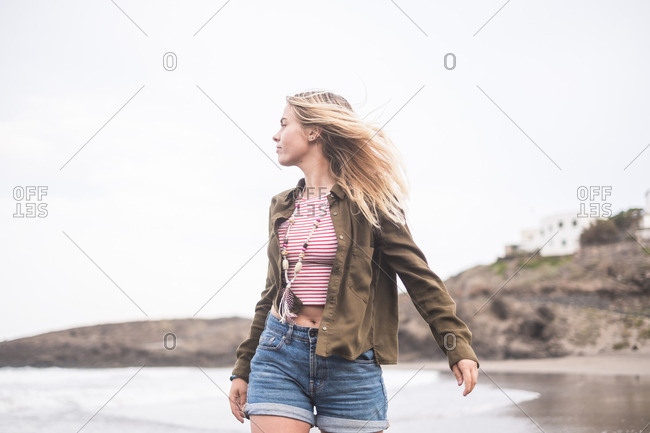Blond young woman walking on the beach looking at distance