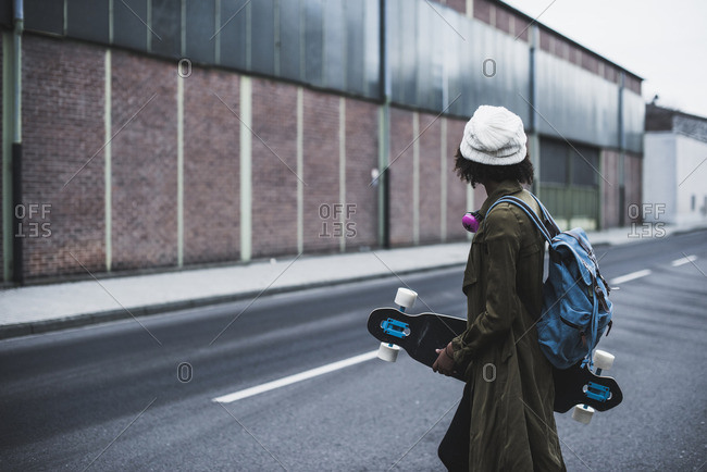 Young woman with headphones- backpack and skateboard on the street