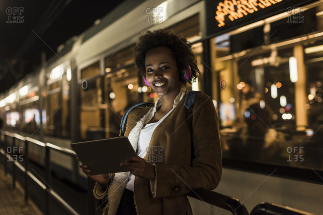 Portrait of smiling young woman with headphones and tablet waiting at the tram stop