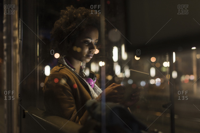 Young woman with tablet waiting at the tram stop by night