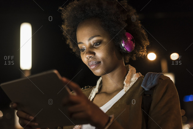 Portrait of young woman with headphones and tablet waiting at the tram stop by night