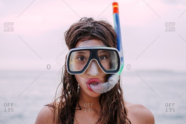 Young woman with diving goggles and snorkel pulling funny faces