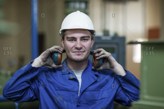 Portrait of worker with helmet and ear muffs in factory