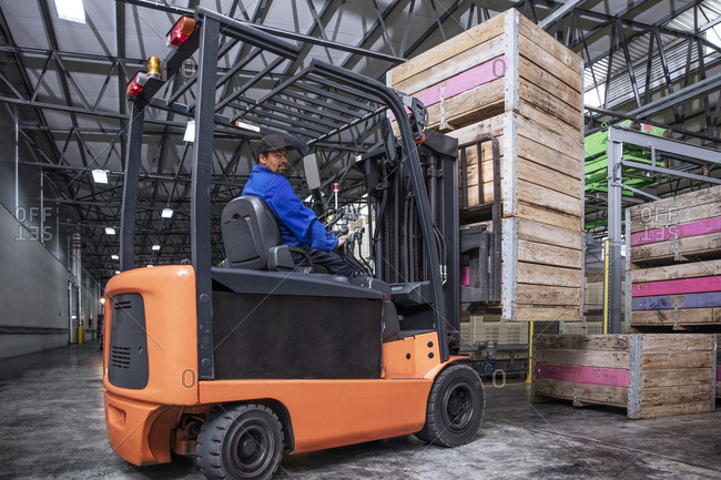 Man on forklift in factory hall stock photo - OFFSET
