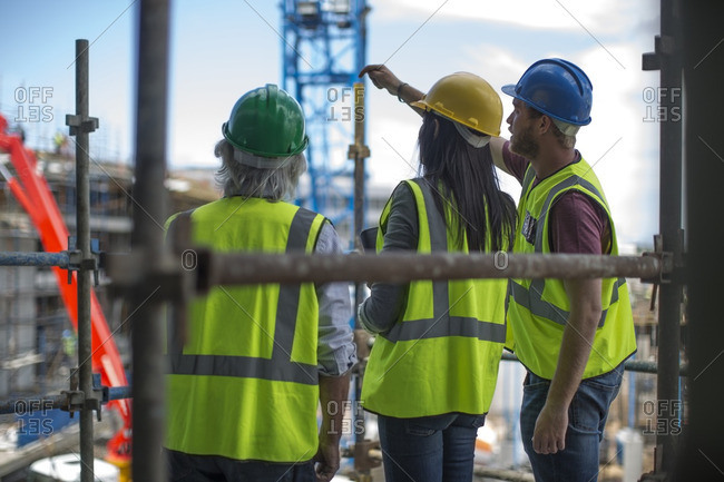 Construction worker talking to man and woman on a construction site
